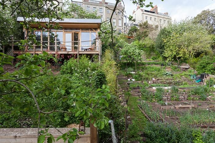 แบบบ้านไม้ยกพื้น มีระเบียงหน้าบ้าน ล้อมรอบด้วยสวน ต้นไม้