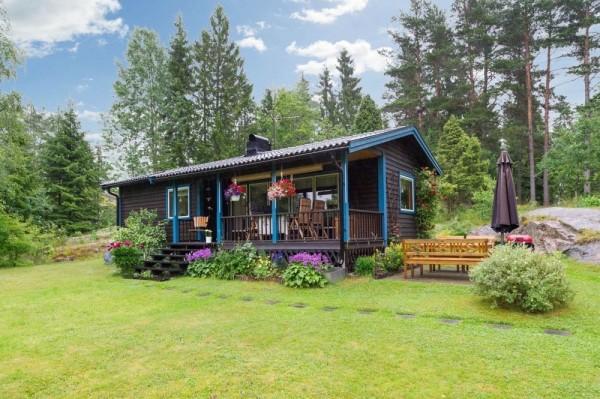 บ้านไม้ยกพื้นหลังเล็ก มีระเบียง และสนามหญ้าหน้าบ้าน