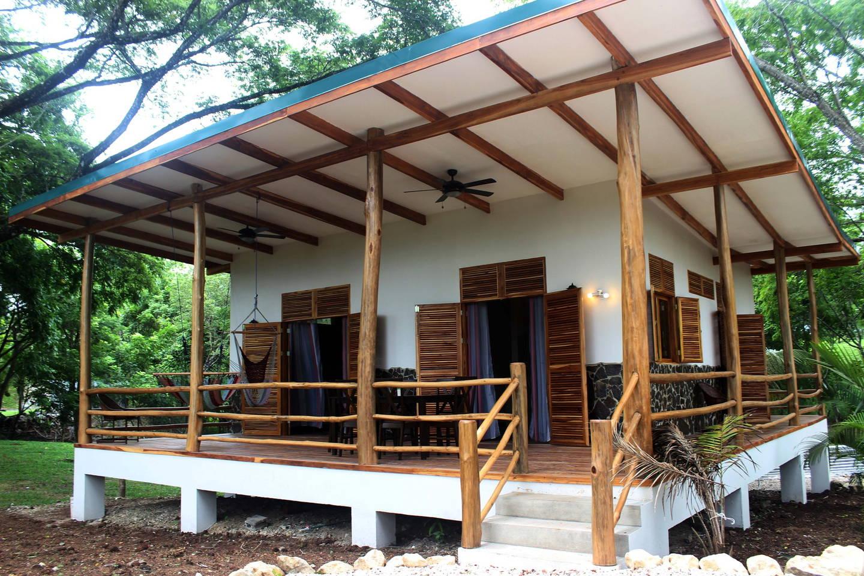 บ้านยกพื้นหลังเล็ก ๆ มีระเบียงไม้สวยงาม ในบรรยากาศใต้ร่มไม้ใหญ่