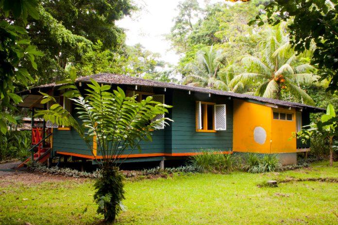 บ้านไม้ยกพื้น ทาผนังสีเขียวเข้ม สวยงามท่ามกลางสวนที่ร่มรื่น