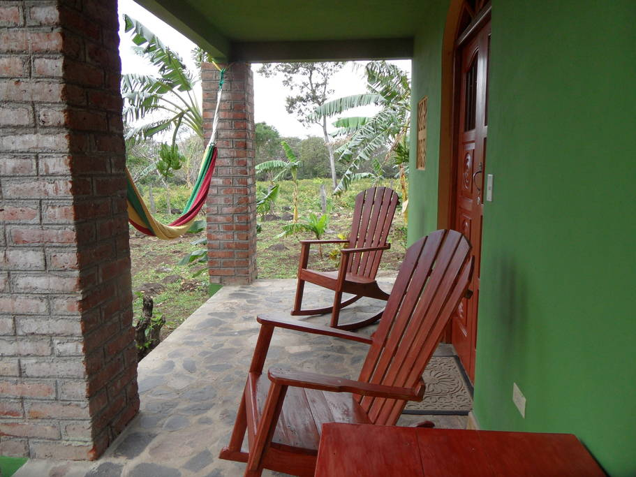 แบบบ้านปูนสองชั้น ทาผนังสีเขียว มีสวนต้นไม้และพืชผักรอบบ้าน