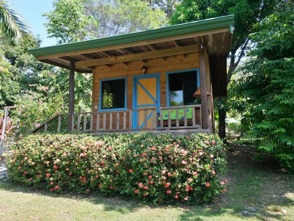 บ้านไม้หลังเล็กยกพื้น มีระเบียงด้านหน้า พร้อมจัดสวนสวย