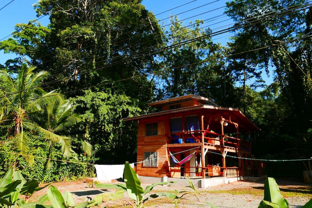 บ้านไม้สองชั้น มีระเบียงชั้นบน-ล่าง อยู่ท่ามกลางธรรมชาติและวิถีชีวิตแบบชนบท