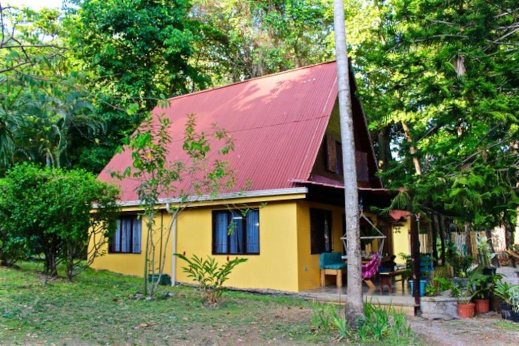 บ้านครึ่งปูนครึ่งไม้ชั้นครึ่ง หลังเล็ก เรียบง่าย สวยงามด้วยเสาไม้เฉลียงหน้าบ้าน