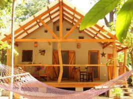 บ้านยกพื้นหลังเล็ก หลังคาหน้าจั่วสามเหลี่ยม มีระเบียงไม้ที่สวยงามด้านหน้า บรรยากาศสงบ ร่มรื่น