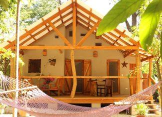 บ้านยกพื้นหลังเล็ก มีระเบียงไม้ที่สวยงามด้านหน้า บรรยากาศสงบ ร่มรื่น
