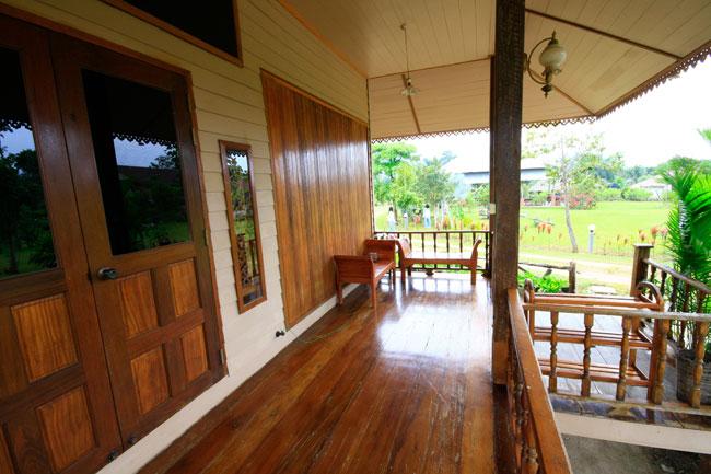 บ้านยกพื้นหลังเล็ก หน้าต่างไม้แบบเรือนไทยโบราณ มีระเบียงนั่งเล่นด้านหน้า