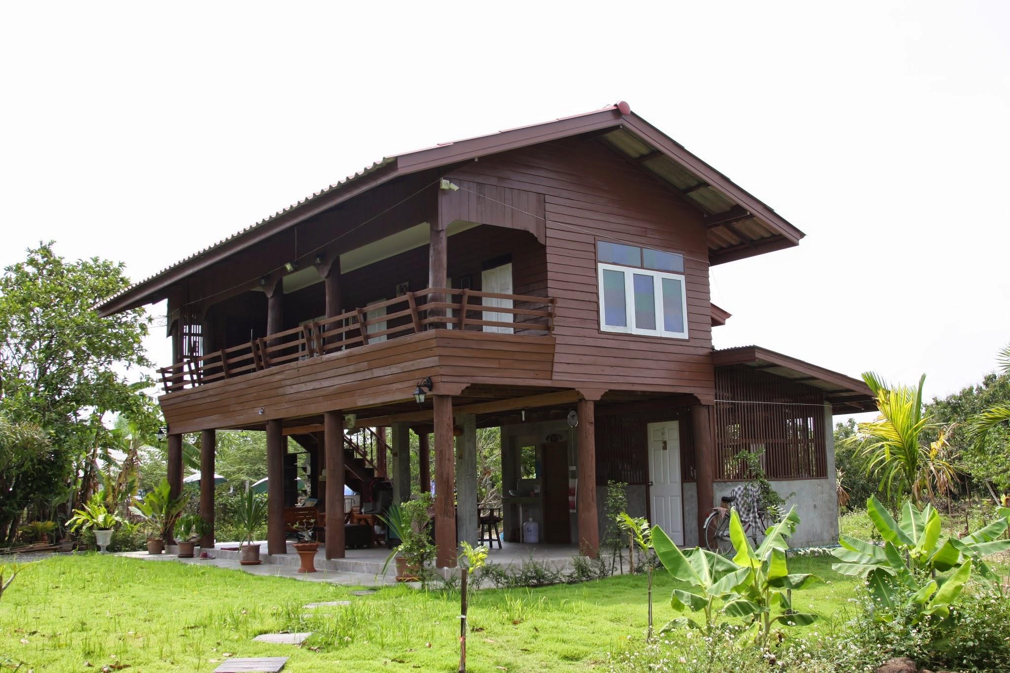 บ้านไม้สักยกพื้นสูงกึ่งปูนเปลือย ชั้นบนมีระเบียงนั่งเล่นชมวิวสวน
