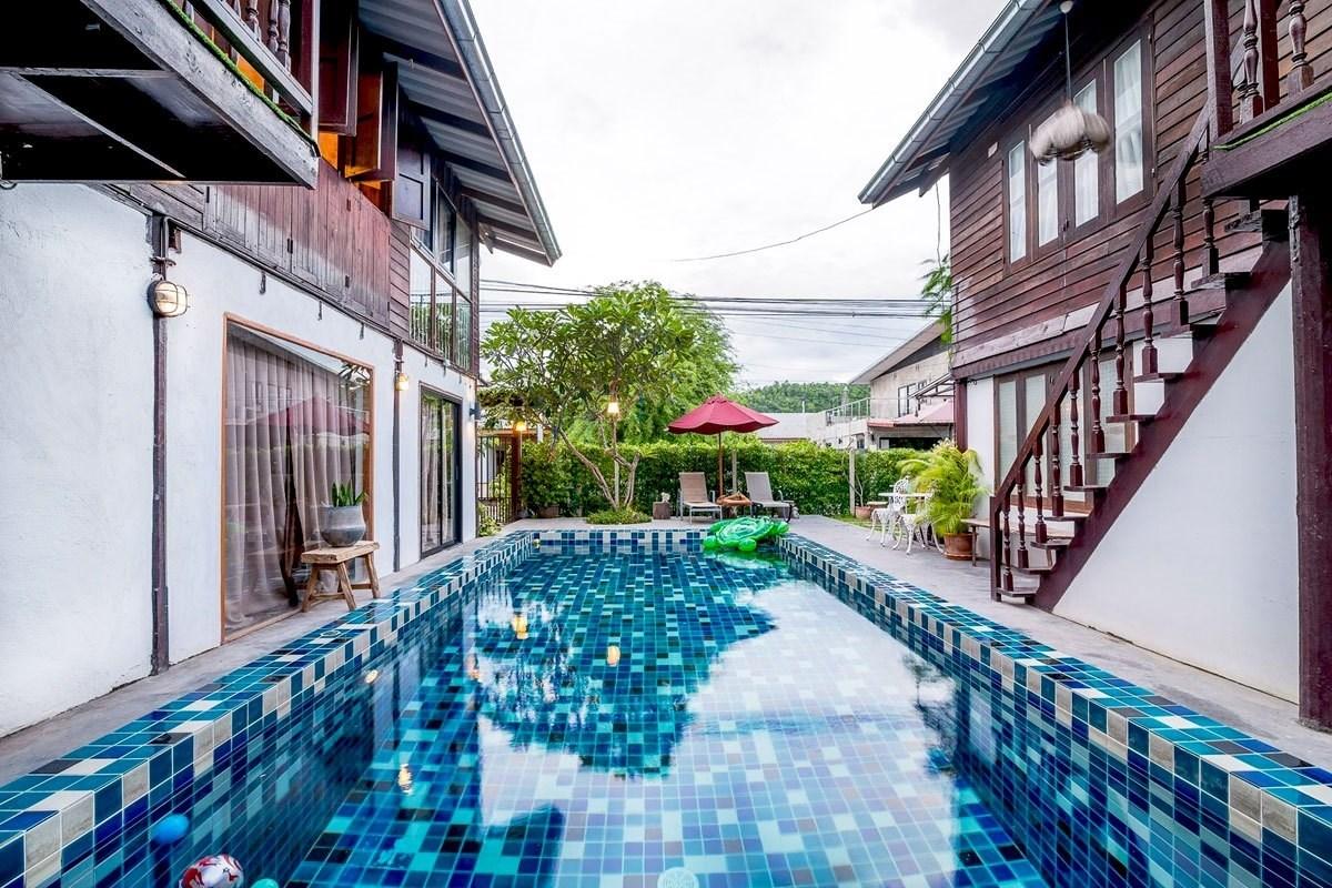บ้านครึ่งปูนครึ่งไม้ แบบ 2 ชั้น 2 หลัง ทำสะพานเชื่อมเข้าหากัน มีสระว่ายน้ำตรงกลาง