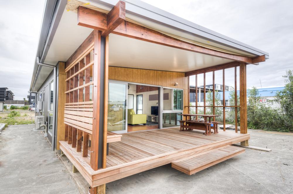 แบบบ้านทรงโมเดิร์น มีเฉลียงไม้เป็นพื้นที่นั่งเล่นแบบเปิดโล่งด้านหน้า ห้องเชื่อมต่อเป็นแนวยาว สวยงาม