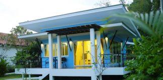 แบบบ้านโมเดิร์นยกพื้น มีระเบียงด้านหน้า-ด้านข้าง ประตูหน้าต่างกระจกใสบานใหญ่ ใช้งบก่อสร้าง 4-5 แสนบาท