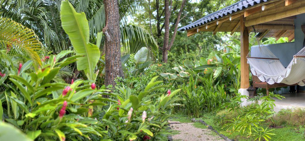 บ้านหลังเล็กสไตล์บังกะโล มีเฉลียงพร้อมผูกเปลนอน ในบรรยากาศสวนทรอปิคอลร่มรื่น