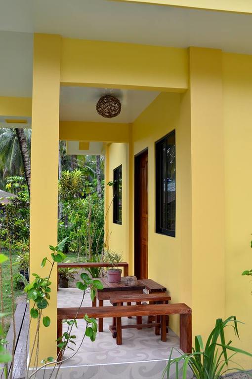 บ้านหลังเล็กสีเหลือง ท่ามกลางสวนมะพร้าว และสนามหญ้าโล่งกว้าง